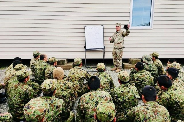 Staff Sgt. Miller provides a convoy security operations brief in Japanese to Soldiers of the Japan Ground Self-Defense Force at Delta Junction, AK, Jun. 2018. The operation was part of bi-lateral training exercise Arctic Aurora in conjunction with 4th Brigade, 25th Infantry Division and 1st Bde, 25th Inf. Div. This was the fourth time Miller was tasked to support a bi-lateral exercise with Japanese forces as a translator. (Photo courtesy of Staff Sgt. Lucas Miller)