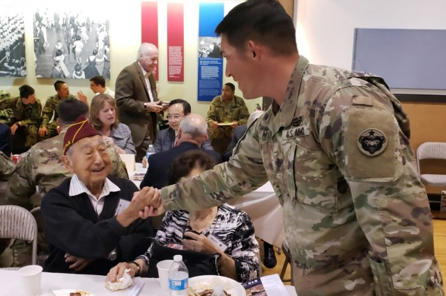 "Staff Sgt. Lucas Miller (center) greets Frank ""Shig"" Tanagi, a Nisei Veteran who was interned at Camp Mindoka and served in the Military Intelligence Service during WWII in Tokyo. The meeting took place during a luncheon at the Nisei Veteran's Committee Memorial Hall in Seattle, Washington, September 10. (U.S. Army Photo by Staff Sgt. Christopher Jelle, 5th Mobile Public Affairs Detachment)"