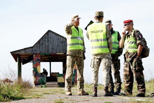 A team of multinational evaluators discuss an upcoming bomb disposal exercise during an Operational Capabilities Concept evaluation at the International Peacekeeping and Security Centre in Yavoriv, Ukraine, Sept. 11, 2018. The evaluation was being conducted by a multinational OCC evaluation team during the Rapid Trident exercise to assess Ukraine's military interoperability capacity.