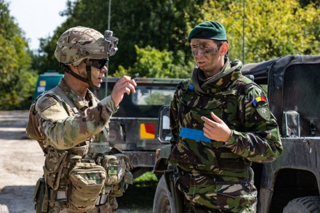 1Lt. Suwaudhaputra speaks with a Romanian Soldier at a checkpoint during Rapid Trident 18 held at Yavoriv CTC, Ukraine, Sept. 10.