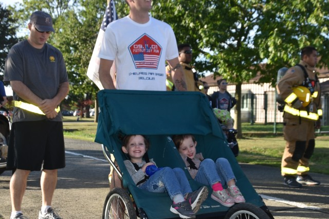 Army Sgt. Zach Beauchamp, assigned to the SHAPE Healthcare Facility, participates in the Patriot 5K Run/Walk with his two daughters Scarlet and Harlee Sept. 11, 2018, on Chievres Air Base, Belgium.