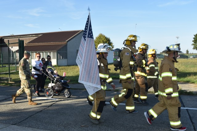 Firefighters from the 424th Air Base Squadron on Chievres Air Base, Belgium, carry an American flag during the Patriot 5K Run/March Sept. 11, 2018.