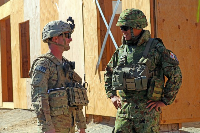 A Soldier from 1st Battalion, 17th Infantry Regiment, 2nd Stryker Brigade Combat Team, 2nd Infantry Division and a Soldier from the 1st Infantry Regiment, Japan Ground Self-Defense Force, hold a friendly conversation while on a break, during an urban live fire range for Exercise Rising Thunder 18, at Yakima Training Center, Washington, Sept. 7. This 15-day exercise helps enhance Soldiers' tactical skills in order to improve readiness within our units and with the Japan Ground Self-Defense Force. (U.S. Army photo by Staff Sgt. Frances Ariele Tejada)
