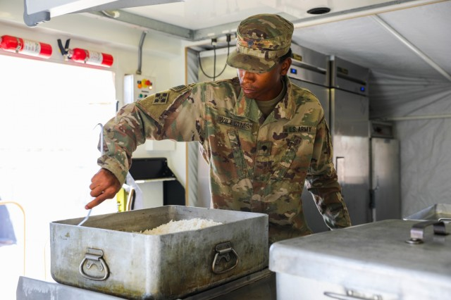 Spc. Kadavius Williams, a culinary specialist assigned to Company J, 1st Battalion, 41st Infantry Regiment, 2nd Infantry Brigade Combat Team, 4th Infantry Division, stirs a container of rice, Sept. 6, 2018, in a mobile kitchen trailer in Tarin Kowt, Afghanistan. Soldiers from Company J provide all personnel on the base with two hot meals a day. (U.S. Army photos by Staff Sgt. Neysa Canfield)