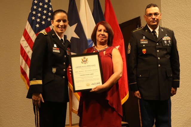 Brig. Gen. Dustin A. Shultz, 1st Mission Support Command, U.S. Army Reserve-PR Commanding General (left), presents an official Certificate of Appreciation to Diana Meléndez (center) in recognition for her support to her husband First Sgt. Eduardo Alvelo Nieves' 33 years of military career, during the command's retirement ceremony celebrated at the Fort Buchanan's Community Club, Sept. 15, 2018.