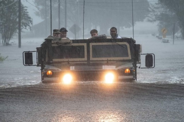 U.S. Army Soldiers help evacuate residents affected by Hurricane Florence with the use of a High Mobility Multi-purpose Wheel Vehicle.