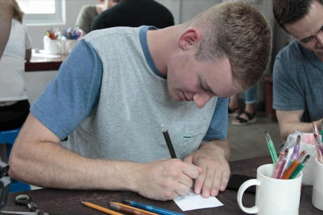 Senior Airman Bryce J. Gavitt, a crew chief with the 51st Maintenance Squadron, draws a design for a ceramic mug at Gaesil Village, South Korea, July 10, 2018. Gavitt and other service members experienced Korean history, culture and cuisine during a cultural tour hosted by the Republic of Korea Ministry of National Defense. These ceramic cups are handmade in the village and take 20 days to cure. (U.S. Army photo by Staff Sgt. Monik Phan)