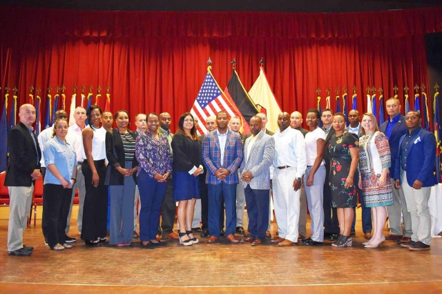 ANSBACH, Germany -- Thirteen NCOs from Installation Management Command -- Europe (IMCOM-E) participated in an induction ceremony at the Ansbach Theater on Bismarck Kaserene this afternoon, Sept. 14.The time-honored ceremony which marks each participant's transition into the Non-Commissioned Officers Corps was hosted by U.S. Army Garrison Ansbach (USAG Ansbach) Command Sgt. Major Philson Tavernier and attended by Command Sgt. Majors representing every Garrison in Europe and IMCOM Euorpe Headquarters: Command Sgt. Maj. Bryant Mason (USAG Italy), Command Sgt. Maj. Michael Sutterfield (USAG Bavaria), Command Sgt. Maj. Chad Pinkston (USAG Wiesbaden), Command Sgt. Maj. Samara Pitre (USAG Benelux), Command Sgt. Maj. Brett Waterhouse (USAG Rheinland Pfalz), Command Sgt. Maj. Toese Tia (USAG Stuttgart) and IMCOM--E Command Sgt. Major Ulysses Rayford (center), who had assembled in Ansbach for their annual Senior NCO Seminar.During the seminar participants met to discuss such issues as Soldier resiliency and development, promotion board standards, barracks management and Soldier mentoring and counseling, among others.
