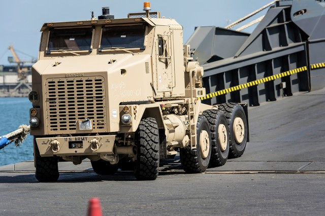 "A newly rebuilt Heavy Equipment Transport truck equipped with C-kit belly-plate armor, or ""golden HET,"" drives off of a shipping vessel and onto a pier at Shuaiba Port, Kuwait, Sept. 11. The truck is part of a large-scale reset effort for more than 50 golden HETs slated to be restored at Red River Army Depot, led by the U.S. Army Tank-automotive and Armaments Command, 1st Theater Sustainment Command, and the 401st Army Field Support Brigade. (U.S. Army photo by Justin Graff, 401st AFSB Public Affairs)"