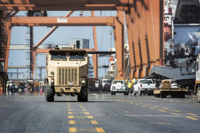 "A newly rebuilt Heavy Equipment Transport truck equipped with C-kit belly-plate armor, or ""golden HET,"" drives along a pier at Shuaiba Port, Kuwait, Sept. 11. The truck is part of a large-scale reset effort for more than 50 golden HETs slated to be restored at Red River Army Depot, led by the U.S. Army Tank-automotive and Armaments Command, 1st Theater Sustainment Command, and the 401st Army Field Support Brigade. (U.S. Army photo by Justin Graff, 401st AFSB Public Affairs)"
