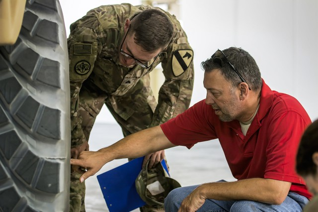 "Randy Weathers (right), TACOM logistics assistance rep., 401st Army Field Support Brigade, and Sgt. Kyle Miller, senior mechanic, 154th Composite Truck Co.-Heavy, 524th Combat Sustainment Support Battalion, conduct a joint Preventative Maintenance Checks and Services (PMCS) inspection on a newly rebuilt Heavy Equipment Transport truck equipped with C-kit belly-plate armor, or ""golden HET,"" at an Army Prepositioned Stocks-5 warehouse, Sept. 14, at Camp Arifjan, Kuwait. (U.S. Army photo by Justin Graff, 401st AFSB Public Affairs)"