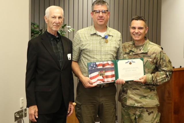 Col. Christopher A Hussin, Commander, U.S. Army Corps of Engineers, Tulsa District, presents Edward N. Johnson (center) the Meritorious Civilian Service Award for his performance while serving as a senior strategic communications advisor to Ukraine's Minster of Defense from 2016 to 2017. Johnson's father Harvey (left) was also in attendance during the ceremony. The Meritorious Civilian Service Award is the second highest award granted by the Secretary of the Army or a major Army commander to civilian personnel.
