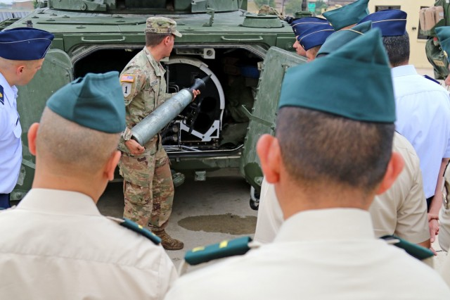 Sgt. John Harrison, a cavalry scout with Quicksilver Troop, 4th Squadron, 3rd Cavalry Regiment, demonstrates how a round is loaded into a Stryker Mobile Gun System during a visit from the Colombian Joint Forces Staff College Sept. 12, 2018, at Fort Hood, Texas.