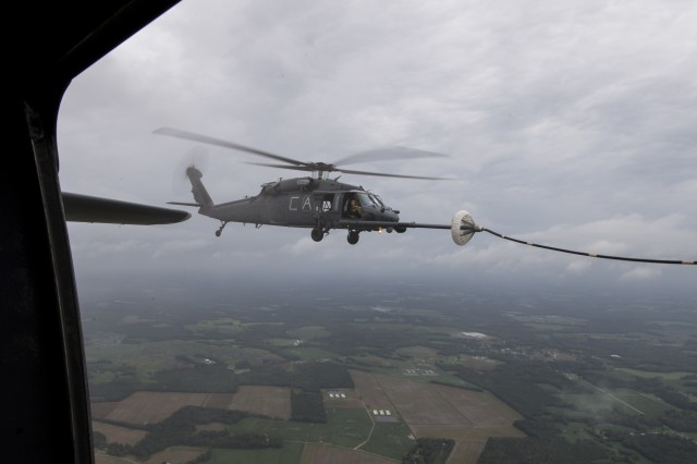 Members from the 106th Rescue Wing New York Air National Guard transfer fuel from a C-130 to a California Air National Guard HH-60 Pave Hawk helicopter over Kinston, N.C. Sept. 16, 2018.