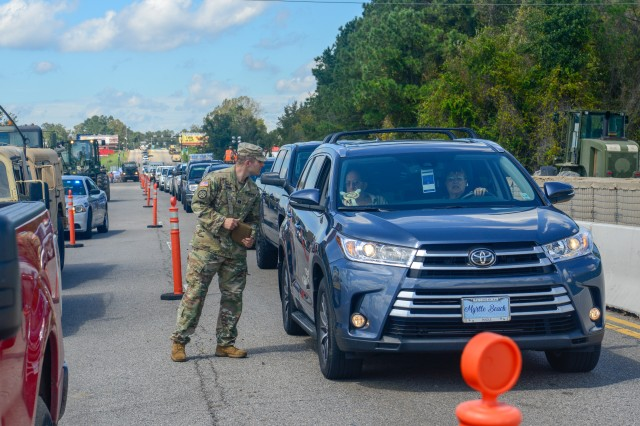 Soldiers with the South Carolina National Guard conduct traffic as they build a barrier to prevent flooding off of Highway 501 in Conway, S.C., Sept. 18, 2018.