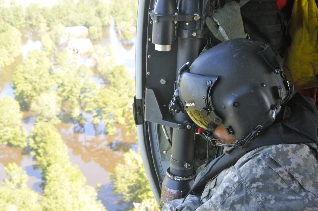 U.S. Army Sgt. 1st Class Frank Palfrey, crew chief with the 28th Expeditionary Combat Aviation Brigade, Pennsylvania National Guard looks out the side of a UH-60 Black Hawk helicopter to identify citizens in need of assistance near Nichols, South Carolina, Sept. 18, 2018.