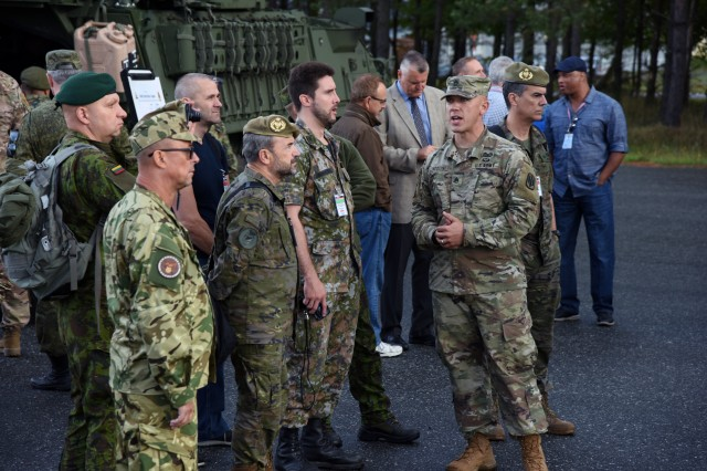 A U.S. Army Soldier explains the High Mobility Artillery Rocket System (HIMARS) to representatives from the Organization of Security and Cooperation in Europe (OSCE) during a treaty compliance demonstration in Grafenwoehr, Germany, Sept. 19, 2018.  The day-two visit to Grafenwoehr fulfills U.S. Army Europe's commitment to provisions of the OSCE's Vienna Document 2011, which requires hosting a visit to a U.S. facility once every five years and demonstrating new types of major weapon and equipment systems within one year of deployment to Europe.  Representatives from 28 countries took part in tours of the Grafenwoehr training facilities, a static display of the HIMARS and a live-fire demonstration of the XM1296 Stryker Infantry Carrier Vehicle-Dragoon (ICV-D), both of which the U.S. Army recently fielded to units in Europe.