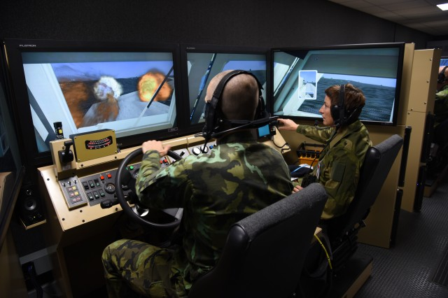 Representatives from the Czech and Norwegian militaries experience a virtual training simulator at the 7th Army Training Command in Grafenwoehr, Germany as part of an Organization for Security Cooperation in Europe treaty compliance visit here, Sept. 18, 2018.  The 2-day visit fulfills the U.S. Army's commitment to provisions of the Vienna Document 2011, which requires hosting a visit to a military facility once every five years and demonstrating new types of major weapon systems and equipment within one year of deployment to Europe.  Representatives from 28 countries took part in the visit.
