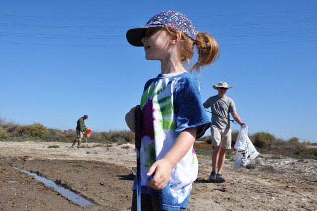 Amelia Jones, 4, foreground, looks off into the distance, as her father, Chris, background left, and her uncle, Andrew Hardison, background right, pick up trash during the Santa Ana River Marsh Cleanup Day Sept. 15 in Newport Beach, California. The event was part of California Coastal Cleanup Day.