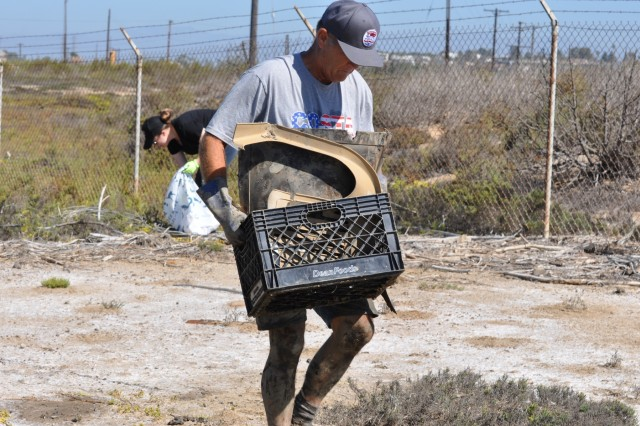 Gary Reynolds of Costa Mesa, California, hauls off a crate of trash during the Santa Ana River Marsh Cleanup Day Sept. 15 in Newport Beach, California. The event was part of California Coastal Cleanup Day.