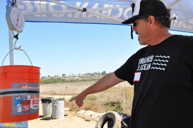 Seth Matson, a volunteer from Drains to Ocean, points to an area to put trash after it is weighed during the Santa Ana River Marsh Cleanup Day Sept. 15 in Newport Beach, California. The event was part of California Coastal Cleanup Day.