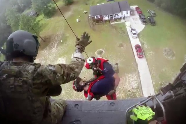 Pararescue Airmen Tech Sgt. Ryan Dush and Staff Sgt. Griffin Elzey, both members of the New York Air National Guard 106th Rescue Wing, are lowered out of a HH-60 Pave Hawk helicopter assigned to the wing during a rescue mission in Lumberton, North Carolina on Sept. 17, 2018 in this still from a helmet mounted video camera. The two Airmen were descending to make an assessment of how many people were in the house, surrounded by flood waters and the best way to get them out. Eventually 15 people were rescued by two HH-60s, one flown by New York Air Guardsmen and the other by an aircrew from the California Air National Guard 129th Rescue Wing.