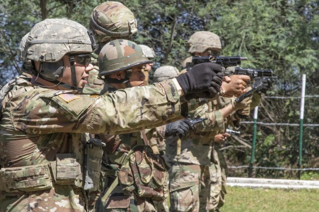 A Soldier with 1st Battalion, 23rd Infantry Regiment, fires a 9 mm pistol with his Indian counterparts from the 99th Mountain Brigade at a reflex range Sept. 19, 2018, at Chaubattia Military Station, India. This was part of Yudh Abhyas, an exercise that enhances the joint capabilities of both the U.S. and Indian army through training and cultural exchange, and helps foster enduring partnerships in the Indo-Asia Pacific region. (U.S. Army photo by Staff Sgt. Samuel Northrup)
