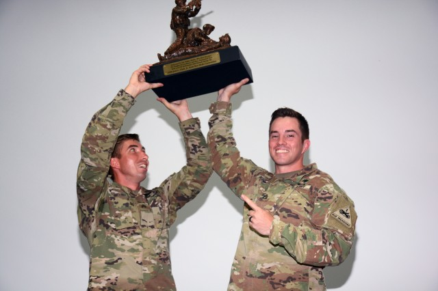 Staff Sgt. Cory Glasgow and Staff Sgt. Branden Mettura, 1st Armor Division, hoist up their trophy after winning the U.S. Army Best Medic Competition Sept. 20, 2018.