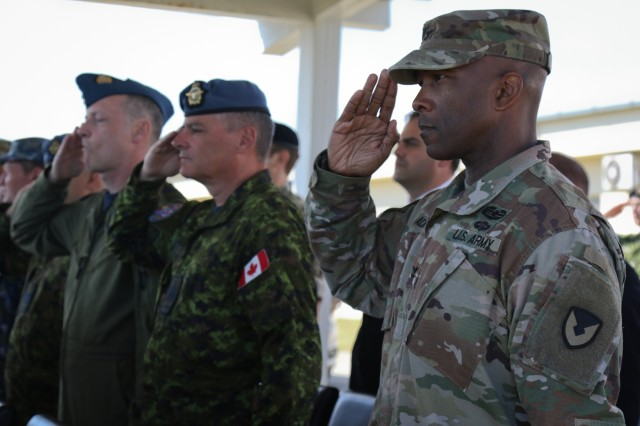 U.S., Canadian and Romanian service members, local civic leaders and civilians salute during the change of command ceremony at the Mihail Kogalniceanu Air Base in Romania, Sept. 17, 2018. U.S. Army Col. Wesley Murray assumed command of the Black Sea Area Support Team in place of U.S. Army Col. James McGlaughn. (U.S. Army National Guard photo by Spc. Hannah Tarkelly, 382nd Public Affairs Detachment/ 1st ABCT, 1st CD/Released)