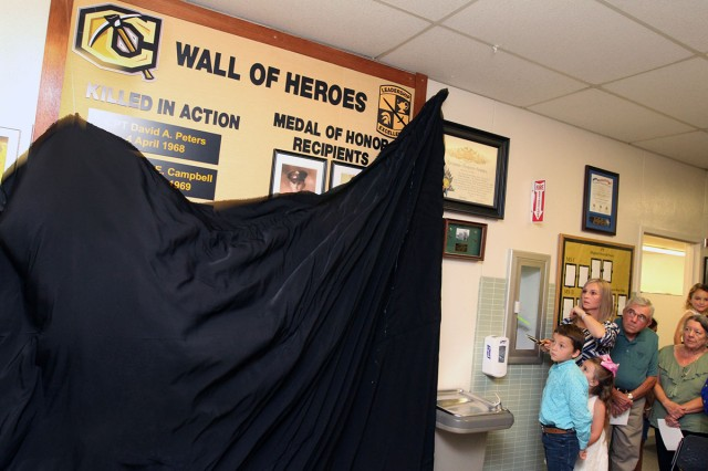 Miranda Landrum (holding scissors) cuts a string to unveil Cameron University's ROTC Wall of Heroes Sept. 14, 2018, on the campus at Burch Hall. Her late-husband, 1st Lt. Brandon Landrum is one of two Fort Sill Soldiers whose names are on the wall. Behind Miranda is Curtis Peters, whose brother David is listed on the wall. The Alexander family also participated in the unveiling.