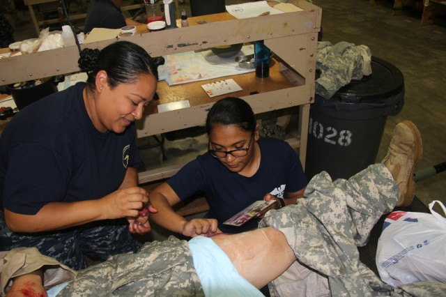 Sailors work on applying moulage to a role-player Aug. 13, 2018, at Regional Training-Site-Medical at Fort McCoy, Wis. RTS-Medical is supporting both unit and collective training during Global Medic, which coincided with Combat Support Training Exercise 86-18-02. (U.S. Army photo by Aimee Malone, Public Affairs Office, Fort McCoy, Wis.)