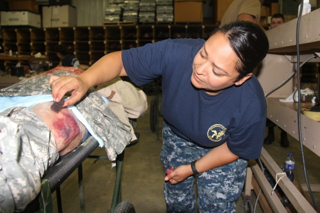 A Sailor works on applying moulage to a role-player Aug. 13, 2018, at Regional Training-Site-Medical at Fort McCoy, Wis. RTS-Medical is supporting both unit and collective training during Global Medic, which coincided with Combat Support Training Exercise 86-18-02. (U.S. Army photo by Aimee Malone, Public Affairs Office, Fort McCoy, Wis.)