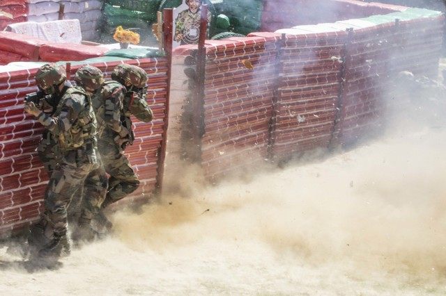 Soldiers with the Indian army brace themselves as they detonate an explosive to clear a doorway to a shoot house Sept. 21, 2018, at Chaubattia Military Station, India. This was part of Yudh Abhyas, an exercise that enhances the joint capabilities of both the U.S. and Indian army through training and cultural exchange, and helps foster enduring partnerships in the Indo-Asia Pacific region. (U.S. Army photo by Staff Sgt. Samuel Northrup)