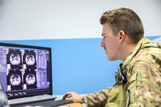 KANDAHAR PROVINCE, Afghanistan (August 5, 2018) -- U.S. Navy Hospital Corpsman 3rd Class Thomas Fite, a radiology technician for Kandahar Airfield NATO Role III Multinational Medical Unit, looks over results of an x-ray, August 5, 2018, to help his Afghan counterparts during a medical advisory visit at Kandahar Regional Military Hospital, Camp Hero in Kandahar, Afghanistan. Staff members from the Role III conduct routine visits to KRMH to train and advise Afghan medical staff. (U.S. Army photo by Staff Sgt. Neysa Canfield/TAAC-South Public Affairs)