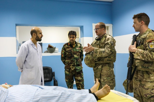 KANDAHAR PROVINCE, Afghanistan (August 5, 2018) -- U.S. Navy Lt. Cdr. Justin S. Clark, radiology technician for Kandahar Airfield NATO Role III Multinational Medical Unit, talks to Afghan radiology technicians, August 5, 2018, during a medical advisory visit at Kandahar Regional Military Hospital, Camp Hero in Kandahar, Afghanistan. Staff members from the Role III conduct routine visits to KRMH to train and advice Afghan medical staff. (U.S. Army photo by Staff Sgt. Neysa Canfield/TAAC-South Public Affairs)