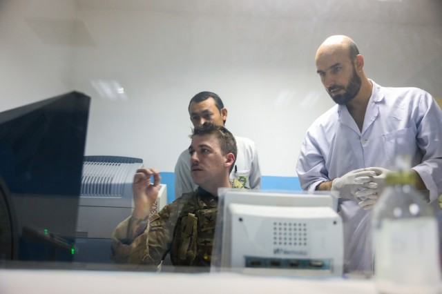 KANDAHAR PROVINCE, Afghanistan (August 5, 2018) -- U.S. Navy Hospital Corpsman 3rd Class Thomas Fite, a radiology technician for Kandahar Airfield NATO Role III Multinational Medical Unit, looks over results of an x-ray, August 5, 2018, to help his Afghan counterparts during a medical advisory visit at Kandahar Regional Military Hospital, Camp Hero in Kandahar, Afghanistan. Staff members from the Role III conduct routine visits to KRMH to train and advice Afghan medical staff. (U.S. Army photo by Staff Sgt. Neysa Canfield/TAAC-South Public Affairs)