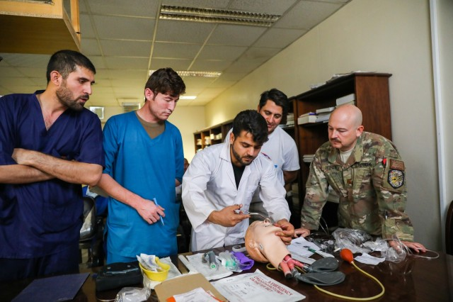 KANDAHAR PROVINCE, Afghanistan (August 5, 2018) -- U.S. Navy Lt. Cdr. Travis J. Fitzpatrick, senior nurse for Kandahar Airfield NATO Role III Multinational Medical Unit, observes as Afghan medical staff members demonstrate how to open an airway, August 5, 2018, during a medical advisory visit at Kandahar Regional Military Hospital, Camp Hero in Kandahar, Afghanistan. Staff members from the Role III conduct routine visits to KRMH to train and advise Afghan medical staff. (U.S. Army photo by Staff Sgt. Neysa Canfield/TAAC-South Public Affairs)