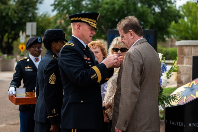Brig. Gen. Darren L. Werner, commanding general of the 13th ESC, pins the Gold Star lapel pin on Greg Kieschnick, son of Chaplain Alton Raymond Kieschnick, who died in 1975 while returning from a training event to Fort Hood, during the 13th ESC memorial rededication ceremony on Sept. 21, 2018 on Fort Hood, Texas. The Kieschnick family was officially recognized as a Gold Star family during the ceremony. Photo by Capt. John Strickland 13th ESC Public Affairs Office
