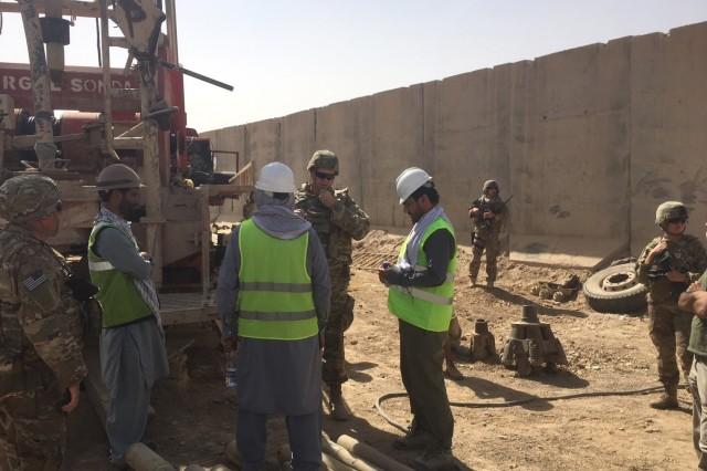 Construction Control Representative, James Fielden, Local National Quality Assurance Representative, and Project Engineer Brian Cagle USACE Afghanistan District discuss the Drilling operations of a new Water Well with the contractors at the Kandahar Air Wing Waste & Water Treatment Project.
