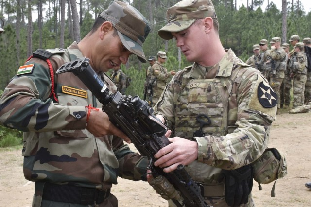 A soldier with U.S. Army's 1st Battalion, 23rd Infantry Regiment, goes of the specification of an M249 Squad Automatic Weapon with a soldier from Indian army's 99th Mountain Brigade Sept. 24, 2018, at Chaubattia Military Station, India. This was part of Exercise Yudh Abhyas 18, a bilateral training scenario designed to foster a shared tactical and technical understanding between the partnered military organizations. (U.S. Army photo by Sgt. Jeff Hibbard)