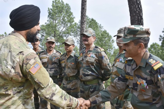 Sgt. Gurpreet Gill, a Soldier with 1-2 Stryker Brigade Combat Team, shakes hands with an Indian army officer Sept. 24, 2018, at Chaubattia Military Station, India. Gill, who is originally from India, was taking part in Yudh Abhyas, an exercise that enhances the joint capabilities of both the U.S. and Indian army through training and cultural exchange, and helps foster enduring partnerships in the Indo-Asia Pacific region. (U.S. Army photo by Sgt. Jeff Hibbard)