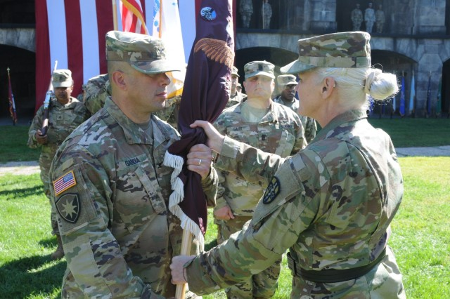 Maj. Gen. Mary Link, Army Reserve Medical Command commanding general, passes the unit colors to Col. Steven Gandia, the incoming commander for Northeast Medical Area Readiness Support Group, headquartered in Staten Island, New York, during a Change of Command ceremony held on Sunday, September 16, 2018. The Change of Command ceremony symbolizes the continuation of leadership and unit identity despite the change of individual authority.  It also represents the transfer of power from one leader to another; passing the ceremonial flag from outgoing to incoming commander is a physical representation of that transfer.