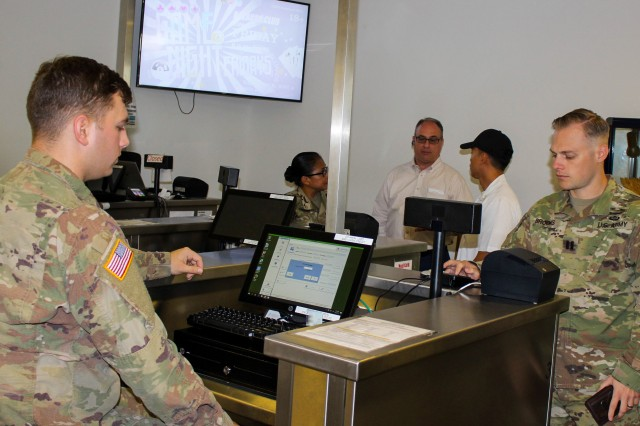 Pvt. Daniel Wilson, 212th Combat Support Hospital, accepts payment from Cpt. Timothy Brocks, 10th Army Air and Missile Defense Command, at the Defender Café dining facility, Rhine Ordnance Barracks, Kaiserslautern, Germany. The Defender Café is one of 14 dining facilities in Europe that recently added credit and debit card payment as an option to their program. (Photo by Rabia Coombs, 405th AFSB)