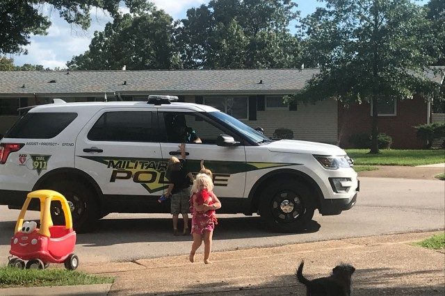 Jason Ploss, Department of the Army Civilian supervisory police officer, hands out stuffed animals to children in one of Fort Leonard Wood's housing areas.
