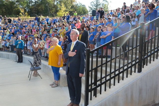 "FORT BENNING, Ga. (Sept. 27, 2018) - Dr. Todd Carver, vice principal of E.A. White Elementary School, and the studentry and staff of E.A. White Elementary School, observe the national anthem. Faculty, staff, students and guests celebrated the grand opening of E. A. White Elementary School at its new location at Sand Hill at Fort Benning, Georgia, Sept. 26, 2018. The new facility serves the Families of military service members who live at Patton Village at Fort Benning. The school is 109,390 square feet and can hold up to 600 students from pre-kindergarten to fifth grade. In addition to having a learning garden, three outdoor amphitheaters, solar panels for hot water, a wind turbine, and an energy dashboard for monitoring utility use, the teaching areas are arranged by grades into ""neighborhoods,"" where the multiple classes within a grade share a space to learn collaboratively. (U.S. Army photos by Markeith Horace, Maneuver Center of Excellence, Fort Benning Public Affairs)"