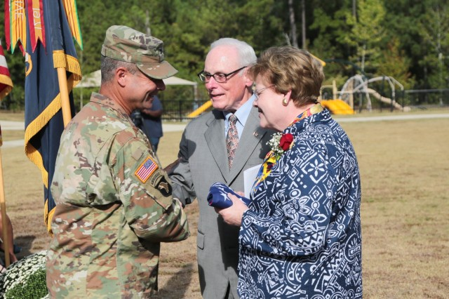 "FORT BENNING, Ga. (Sept. 27, 2018) - From left, Col. Clinton W. Cox, U.S. Army Garrison Fort Benning commander, presents a flag flown over the Pentagon to retired Col. William Rasco and Lucy White Rasco. Lucy White Rasco is the niece of 1st Lt. Edward A. White, for whom the newly opened E.A. White Elementary School is named. Faculty, staff, students and guests celebrated the grand opening of E. A. White Elementary School at its new location at Sand Hill at Fort Benning, Georgia, Sept. 26, 2018. The new facility serves the Families of military service members who live at Patton Village at Fort Benning. The school is 109,390 square feet and can hold up to 600 students from pre-kindergarten to fifth grade. In addition to having a learning garden, three outdoor amphitheaters, solar panels for hot water, a wind turbine, and an energy dashboard for monitoring utility use, the teaching areas are arranged by grades into ""neighborhoods,"" where the multiple classes within a grade share a space to learn collaboratively. (U.S. Army photos by Markeith Horace, Maneuver Center of Excellence, Fort Benning Public Affairs)"
