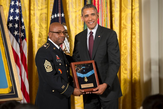 President Barack Obama bestows the Medal of Honor to Sgt. Henry Johnson. Accepting on his behalf is Command Sgt. Maj. Louis Wilson, of the New York National Guard, in the East Room of the White House, June 2, 2015.