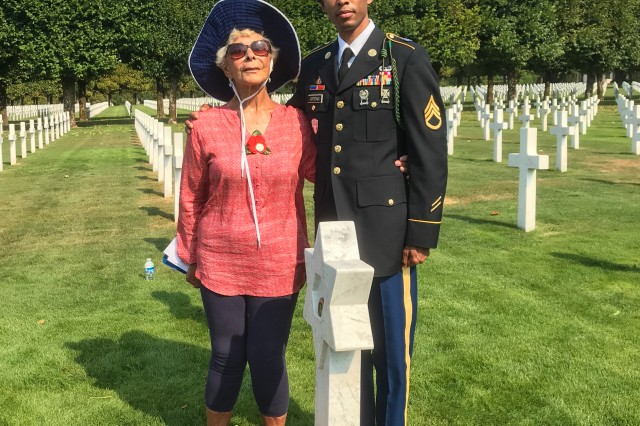 Ina Shemin Bass, Sgt. William Shemin's youngest daughter, stands with Staff Sgt. Jonell Andre Gittens at the Meuse-Argonne Cemetery in France during a visit in August 2018. They placed a basket of flowers, with a red, white and blue remembrance banne,r on the grave of a fellow member of the 47th Infantry, Pvt. Harry Siegel.