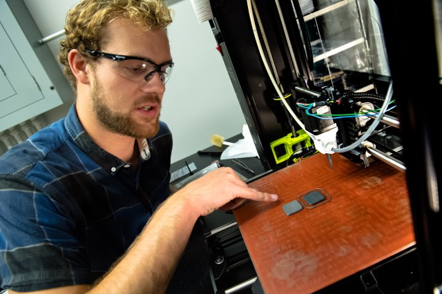 Joshua Pelz, a materials science and engineering doctoral candidate at the University of California San Diego, observes composite ceramic armor samples he created using a custom 3-D printer he designed during his summer working at the U.S. Army Research Laboratory at Aberdeen Proving Ground, Md.