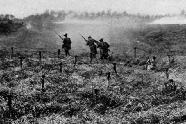New York National Guard Soldiers of the 27th Division 107th Regiment train for the planned attack on the Hindenburg Line, September 1918. In this photograph the Soldiers practice moving through barbed wire obstacles.